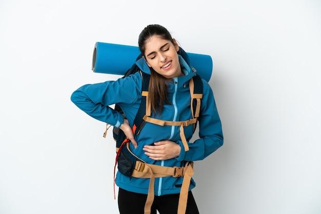Молодой альпинист с большим рюкзаком на изолированном фоне страдает от боли в спине из-за того, что приложил усилие