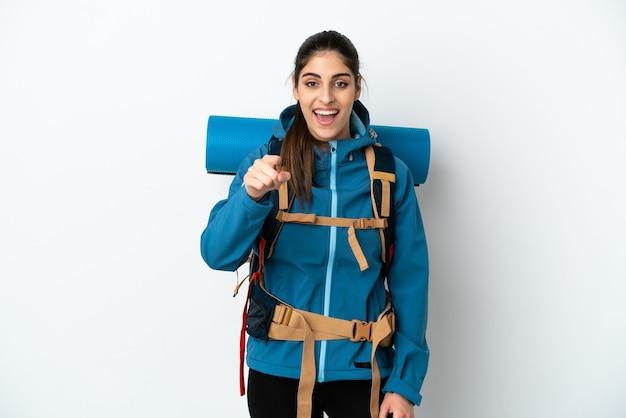 孤立した背景の上に大きなバックパックを持った若い登山家の男は驚いて正面を指しています