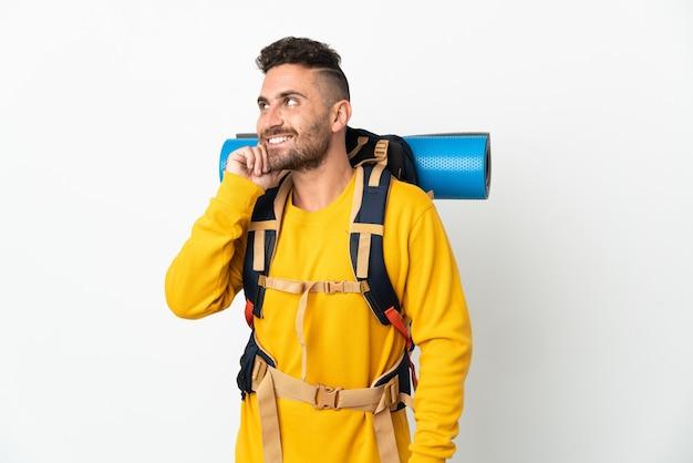 Молодой альпинист с большим рюкзаком на изолированном фоне думает об идее, глядя вверх