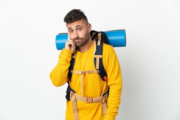 Молодой альпинист с большим рюкзаком на изолированном фоне, думая об идее Premium Фотографии