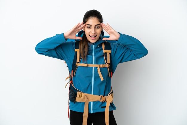 驚きの表現と孤立した背景の上の大きなバックパックを持つ若い登山家の男