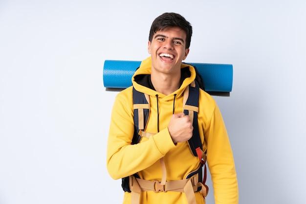 勝利を祝う分離された青の上の大きなバックパックを持つ若い登山家男
