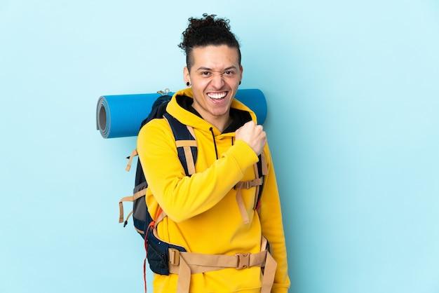勝利を祝う孤立した青い壁の上の大きなバックパックを持つ若い登山家の男