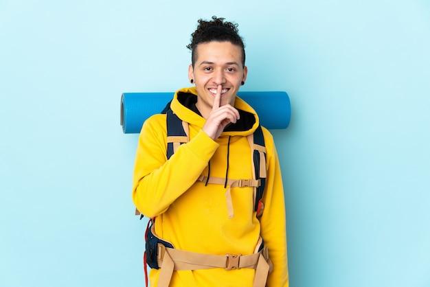 沈黙のジェスチャーをしている孤立した青い壁の上の大きなバックパックを持つ若い登山家の男