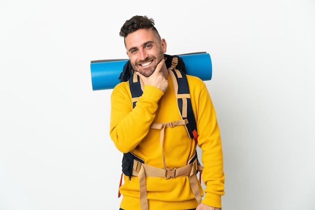 孤立した幸せと笑顔の上に大きなバックパックを持つ若い登山家の男