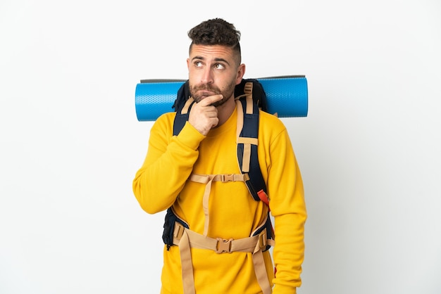 疑いと思考を持って孤立した上の大きなバックパックを持つ若い登山家の男