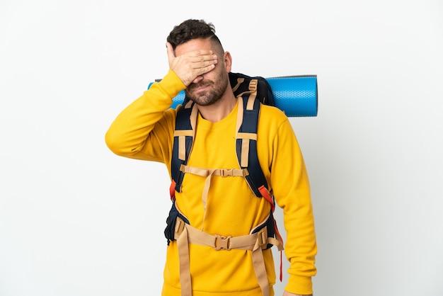 手で目を覆っている孤立した壁の上に大きなバックパックを持つ若い登山家の男。何かを見たくない