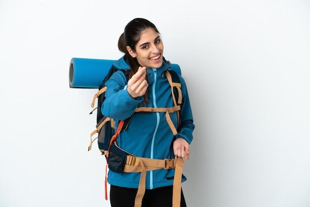 Молодой альпинист с большим рюкзаком над изолированной стеной делает денежный жест