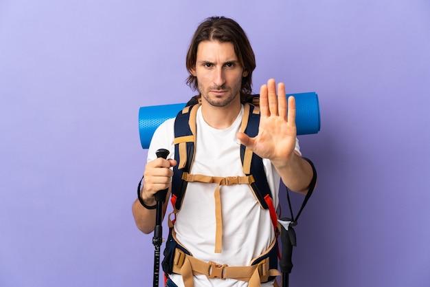 Молодой альпинист с большим рюкзаком над изолированной стеной делает стоп-жест