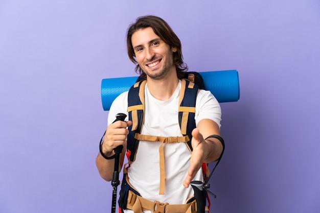 かなり閉じるために握手する孤立した壁の上に大きなバックパックを持つ若い登山家の男