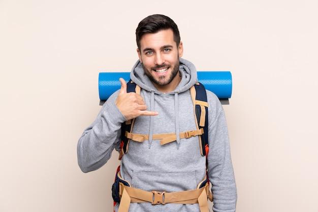 孤立した壁の上の大きなバックパックを持つ若い登山家男