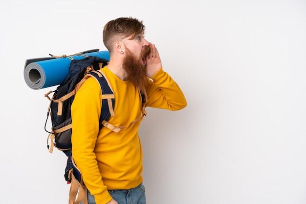Молодой человек альпиниста с большим рюкзаком над изолированной белой кричал с широко открытым ртом