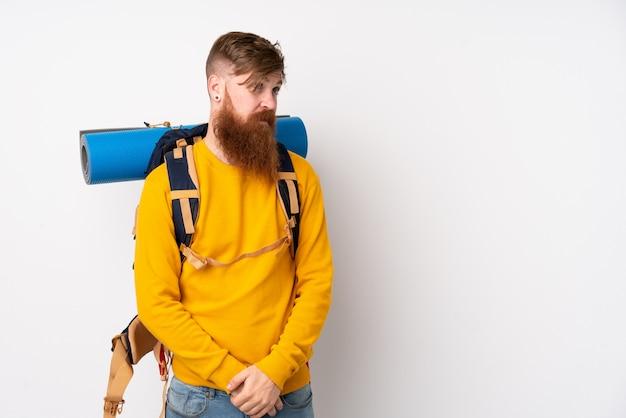 Молодой человек альпиниста с большим рюкзаком над изолированным белым стоял и смотрит в сторону