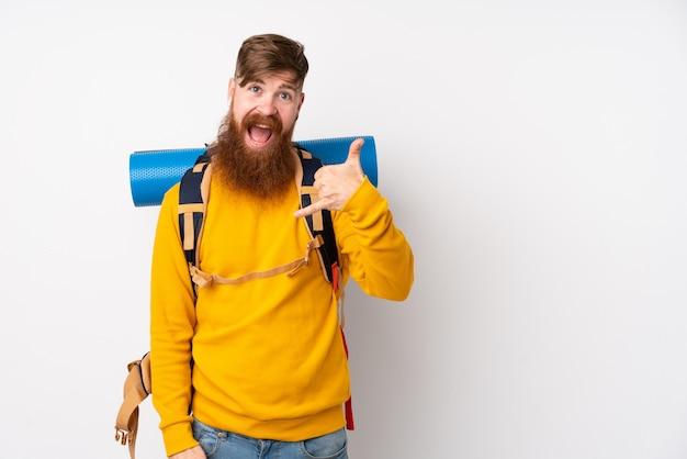 電話ジェスチャーを作る分離の白い壁に大きなバックパックを持つ若い登山家男