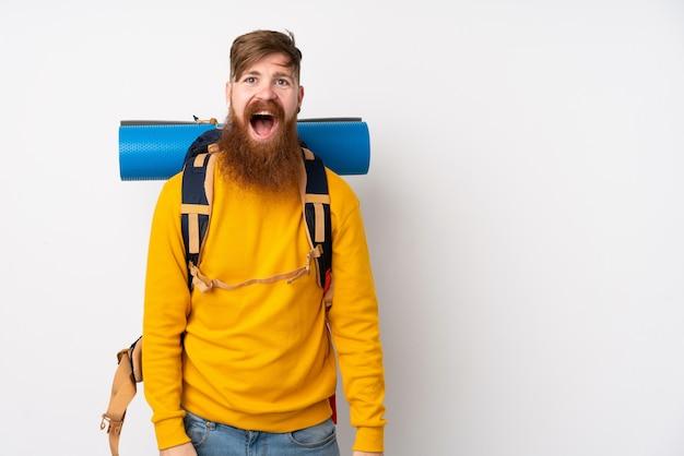 Молодой человек альпиниста с большим рюкзаком на белом фоне с удивленным выражением лица
