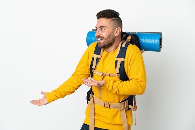 横を見ながら驚きの表情で孤立した大きなバックパックを持つ若い登山家の男