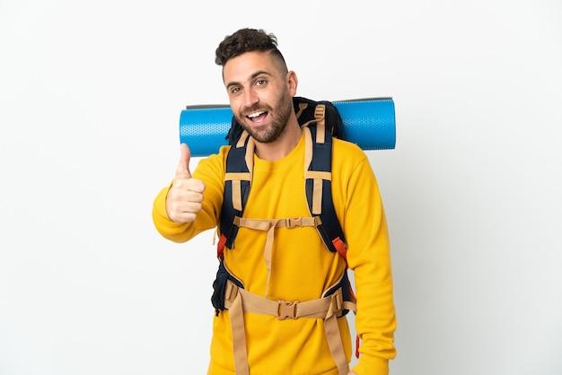 何か良いことが起こったので、親指を立てて孤立した大きなバックパックを持った若い登山家の男