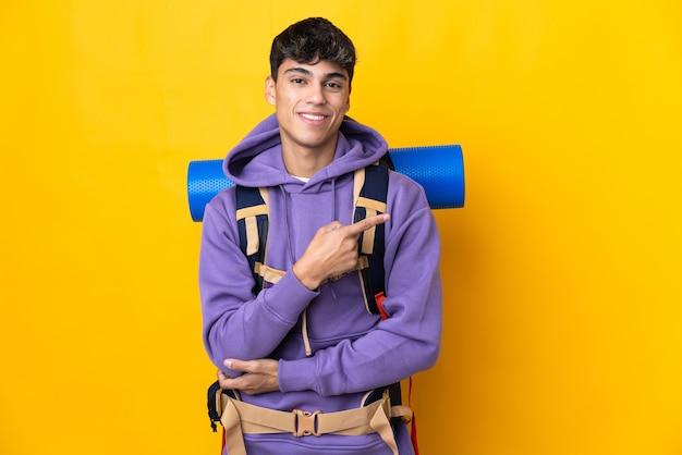 Молодой альпинист с большим рюкзаком на изолированном желтом фоне, указывая в сторону, чтобы представить продукт