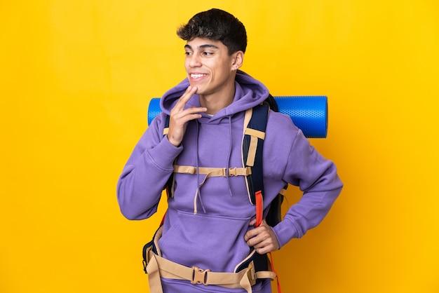 Молодой альпинист с большим рюкзаком над изолированной желтой стеной смотрит вверх, улыбаясь