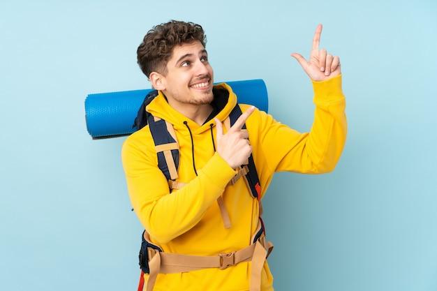 Молодой альпинист с большим рюкзаком, указывая указательным пальцем - отличная идея