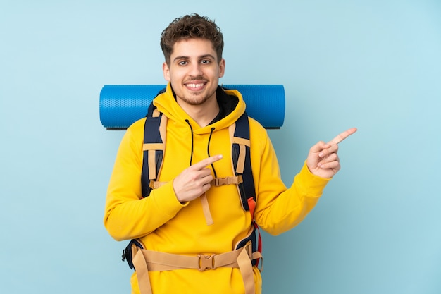 Young mountaineer man with a big backpack on blue  wall pointing finger to the side