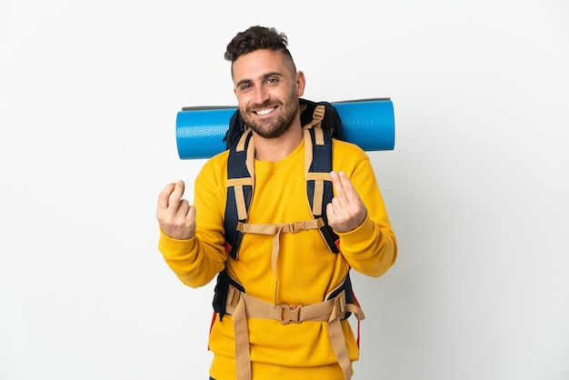 Young mountaineer man with a big backpack over isolated background making money gesture