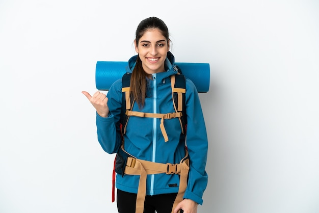 Young mountaineer man with a big backpack over isolated background pointing to the side to present a product