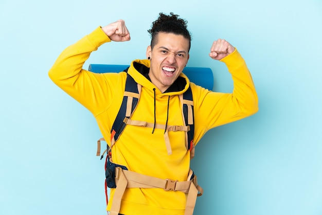 Young mountaineer man with a big backpack over isolated blue background celebrating a victory