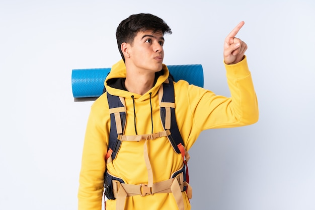 Young mountaineer man with a big backpack over isolated blue background touching on transparent screen