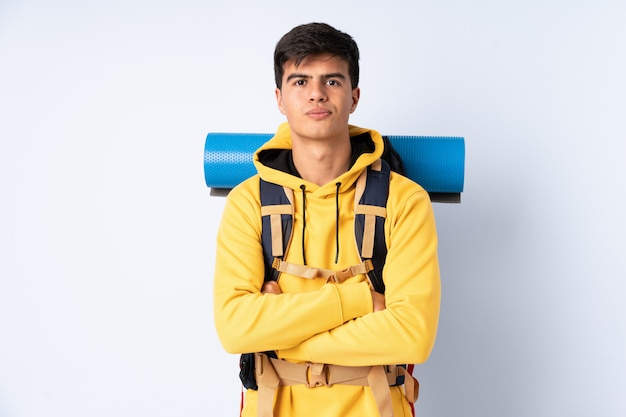 Young mountaineer man with a big backpack over isolated blue keeping arms crossed