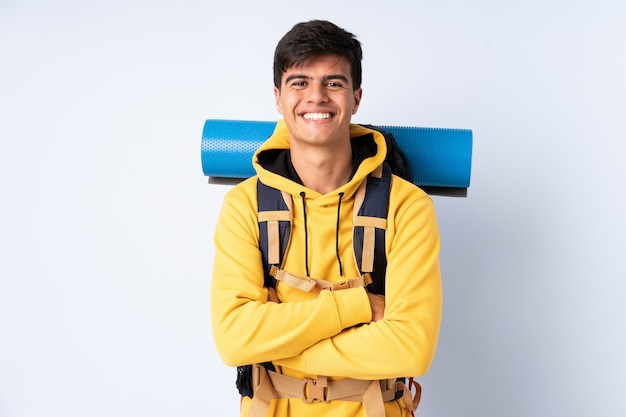 Young mountaineer man with a big backpack over isolated blue laughing