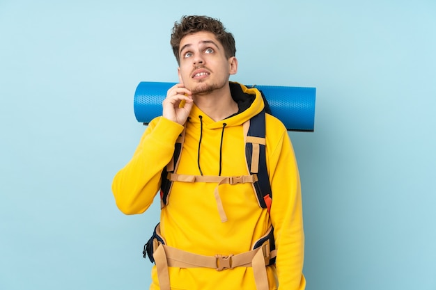 Young mountaineer man with a big backpack isolated on blue thinking an idea
