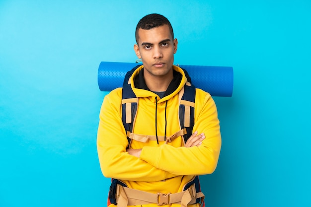 Young mountaineer man with a big backpack over isolated blue wall keeping arms crossed