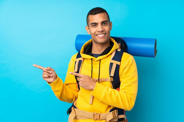 Young mountaineer man with a big backpack over isolated blue wall pointing finger to the side