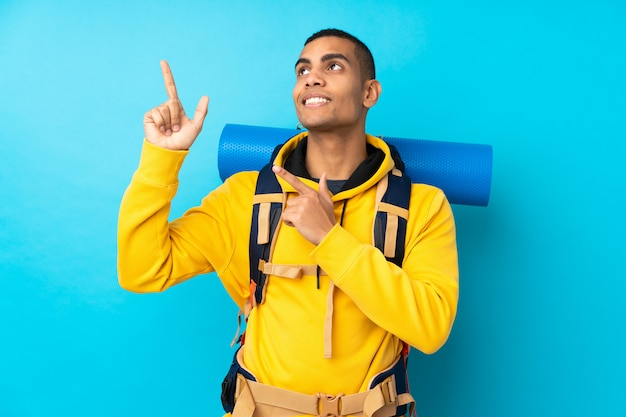 Young mountaineer man with a big backpack over isolated blue wall pointing with the index finger a great idea