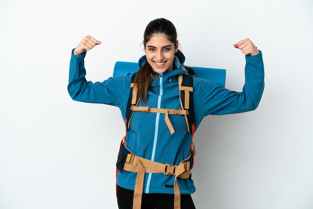 Young mountaineer man with a big backpack over isolated wall doing strong gesture