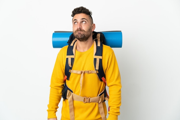 Young mountaineer man with a big backpack over isolated wall and looking up