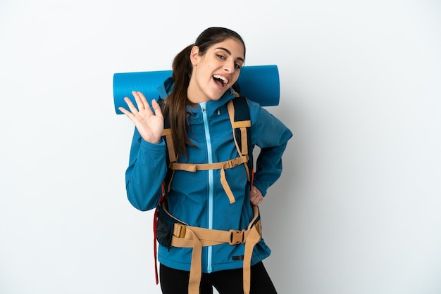 Young mountaineer man with a big backpack over isolated wall saluting with hand with happy expression