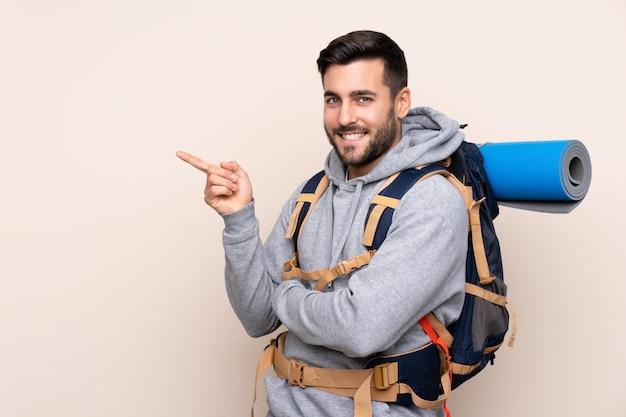 Young mountaineer man with a big backpack over isolated wall