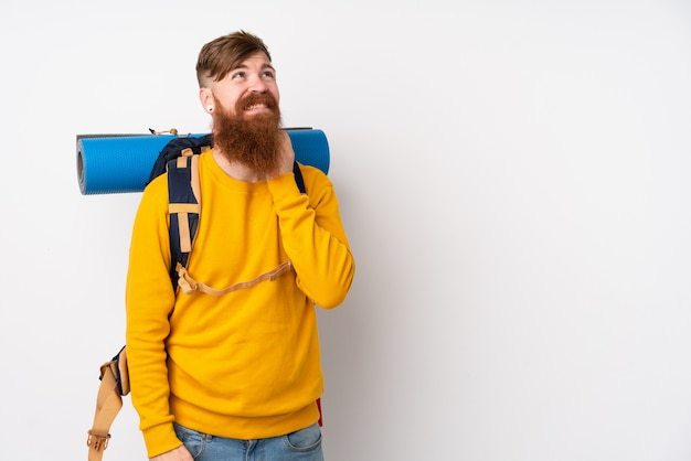 Young mountaineer man with a big backpack over isolated white thinking an idea
