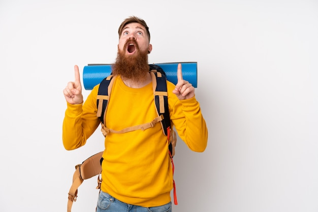 Young mountaineer man with a big backpack over isolated white wall pointing with the index finger a great idea