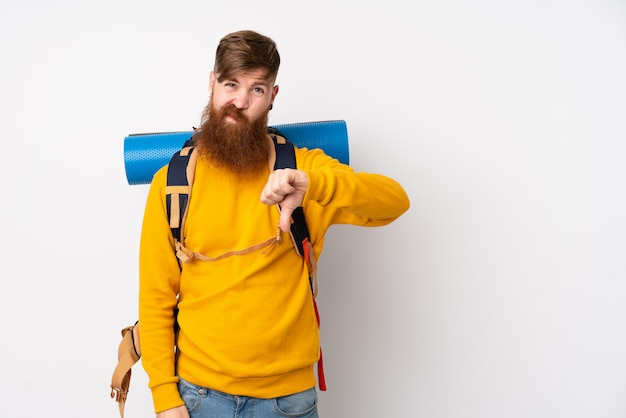 Young mountaineer man with a big backpack over isolated white wall showing thumb down sign