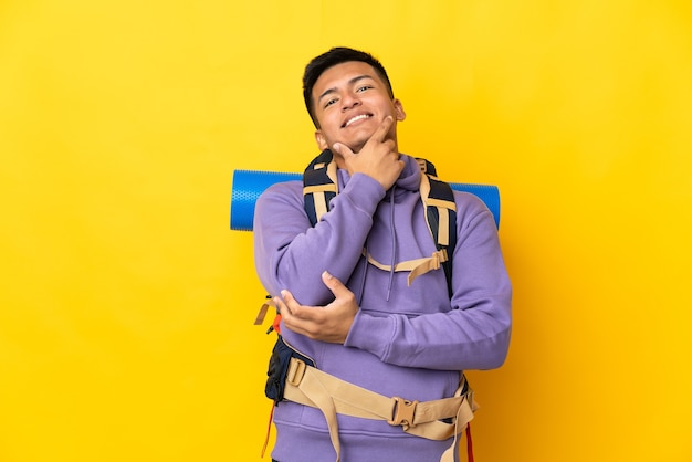 Young mountaineer man with a big backpack isolated on yellow background happy and smiling
