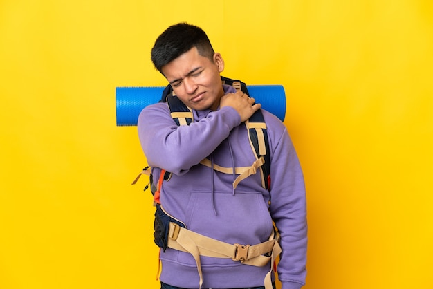 Young mountaineer man with a big backpack isolated on yellow background suffering from pain in shoulder for having made an effort