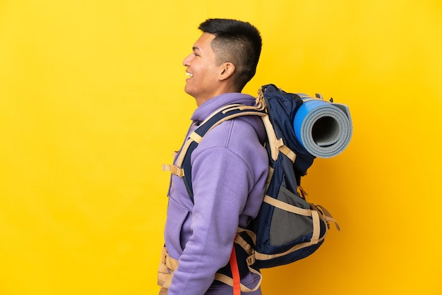 Young mountaineer man with a big backpack isolated on yellow wall laughing in lateral position