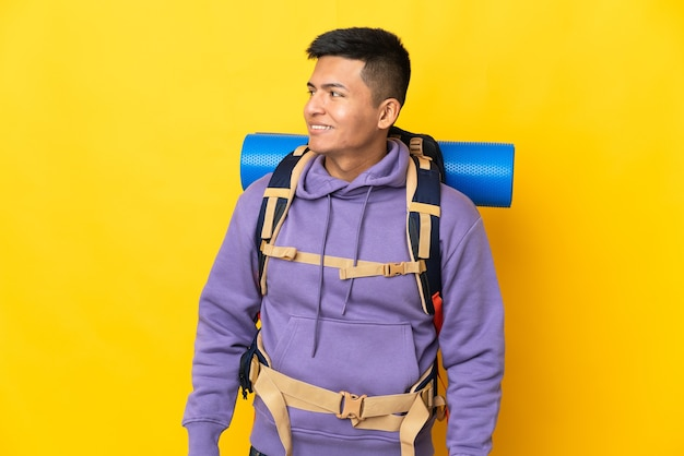 Young mountaineer man with a big backpack isolated on yellow wall looking to the side and smiling