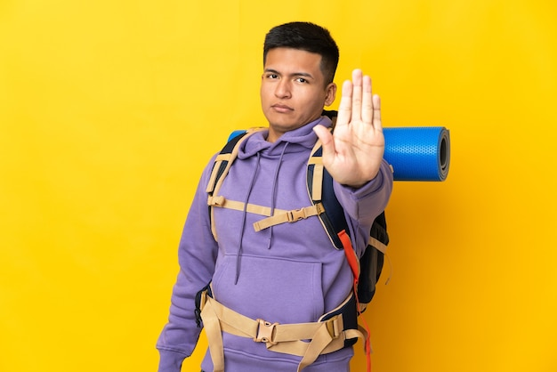 Young mountaineer man with a big backpack isolated on yellow wall making stop gesture
