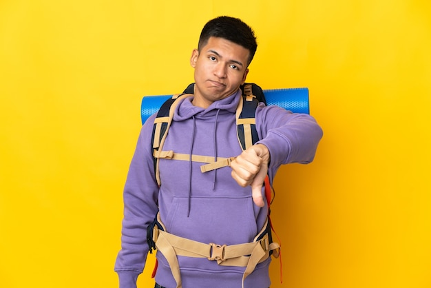 Young mountaineer man with a big backpack isolated on yellow wall showing thumb down with negative expression