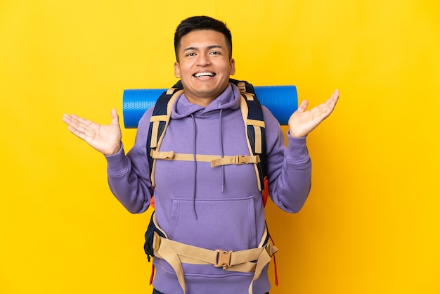 Young mountaineer man with a big backpack isolated on yellow wall with shocked facial expression