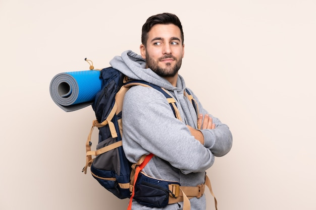 Young mountaineer man with a big backpack laughing